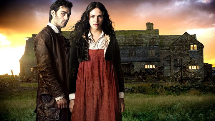 Jem and Mary, from 'Jamaica Inn' stare at the camera. The old inn is in the background.
