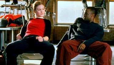 The two characters from 'Save the Last Dance' film. They sit on a chair, slouching.