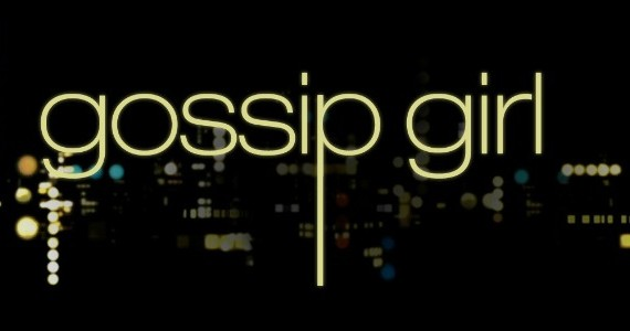 The poster header for the series 'Gossip Girl', written in gold. The background shows New York City's bright lights on a black background.