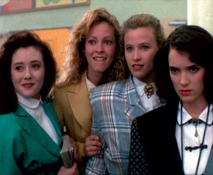 Four girls from the film 'Heathers' whisper conspiratorily
