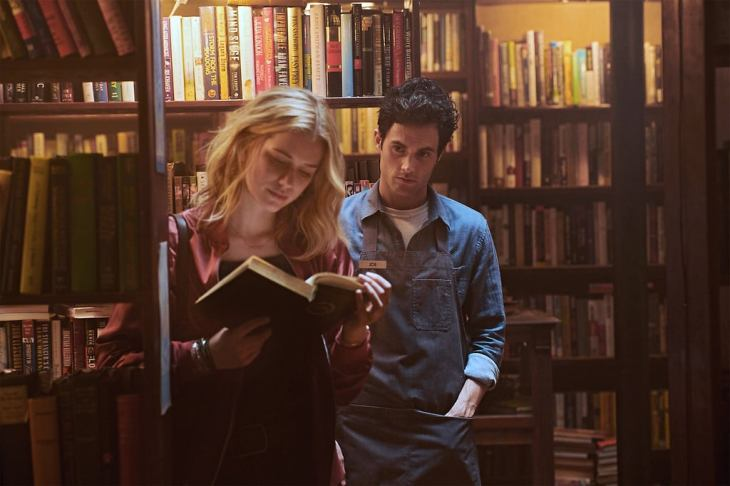 A still from series 'You' on Netflix. A young man peers over a young woman's shoulder as she reads in a bookshop.