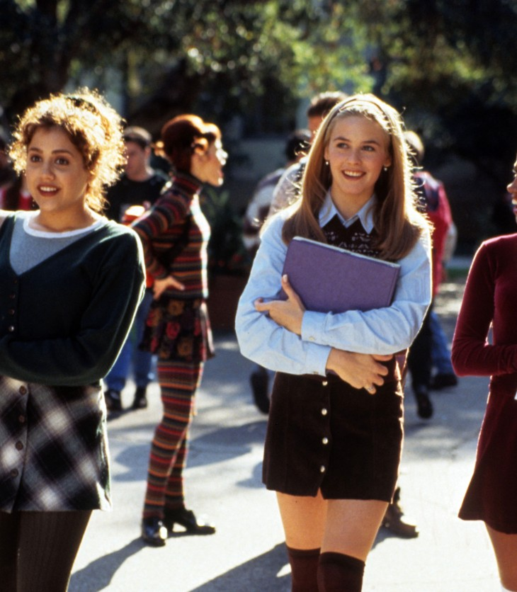 Three school girls laugh and chat as they head into school