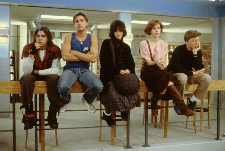 The characters from 'The Breakfast Club' sit on a desk and look in different directions. They look moody and fed-up.