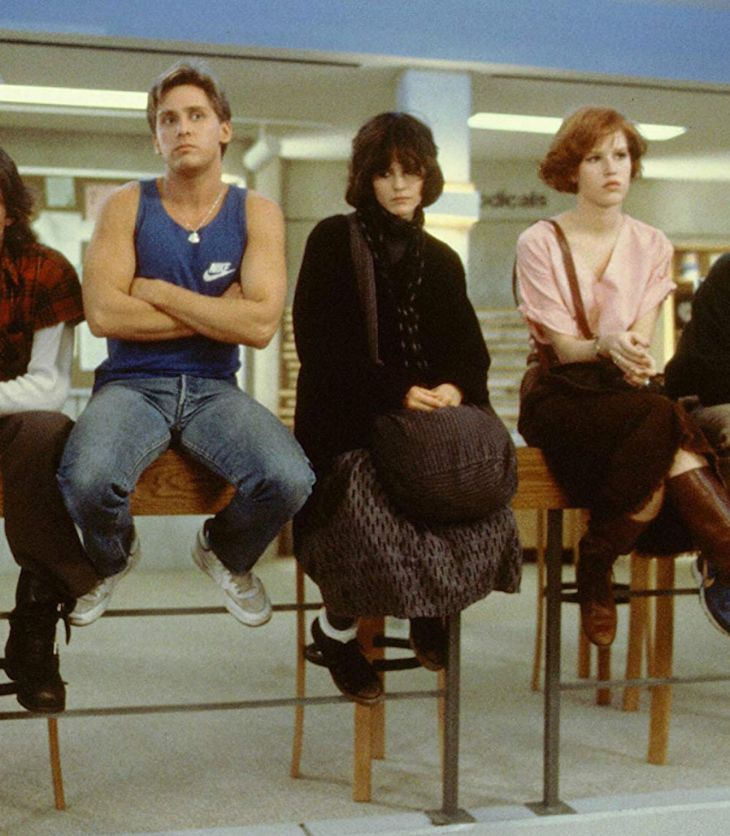 The characters from 'The Breakfast Club' sit on a desk and look in different directions. They look moody and fed-up