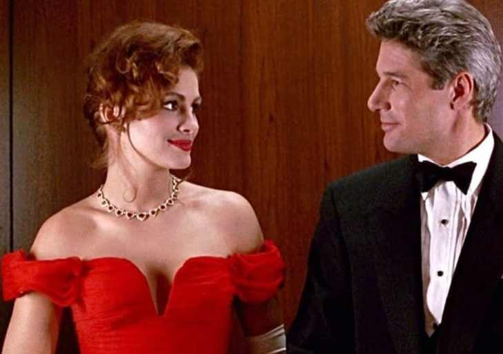 A still from 'Pretty Woman'. Edward and Vivian look at each other. She is wearing a bright red dress and he is wearing a smart suit.