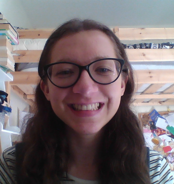 A picture of me smiling into the camera, a bunkbed in the background.
