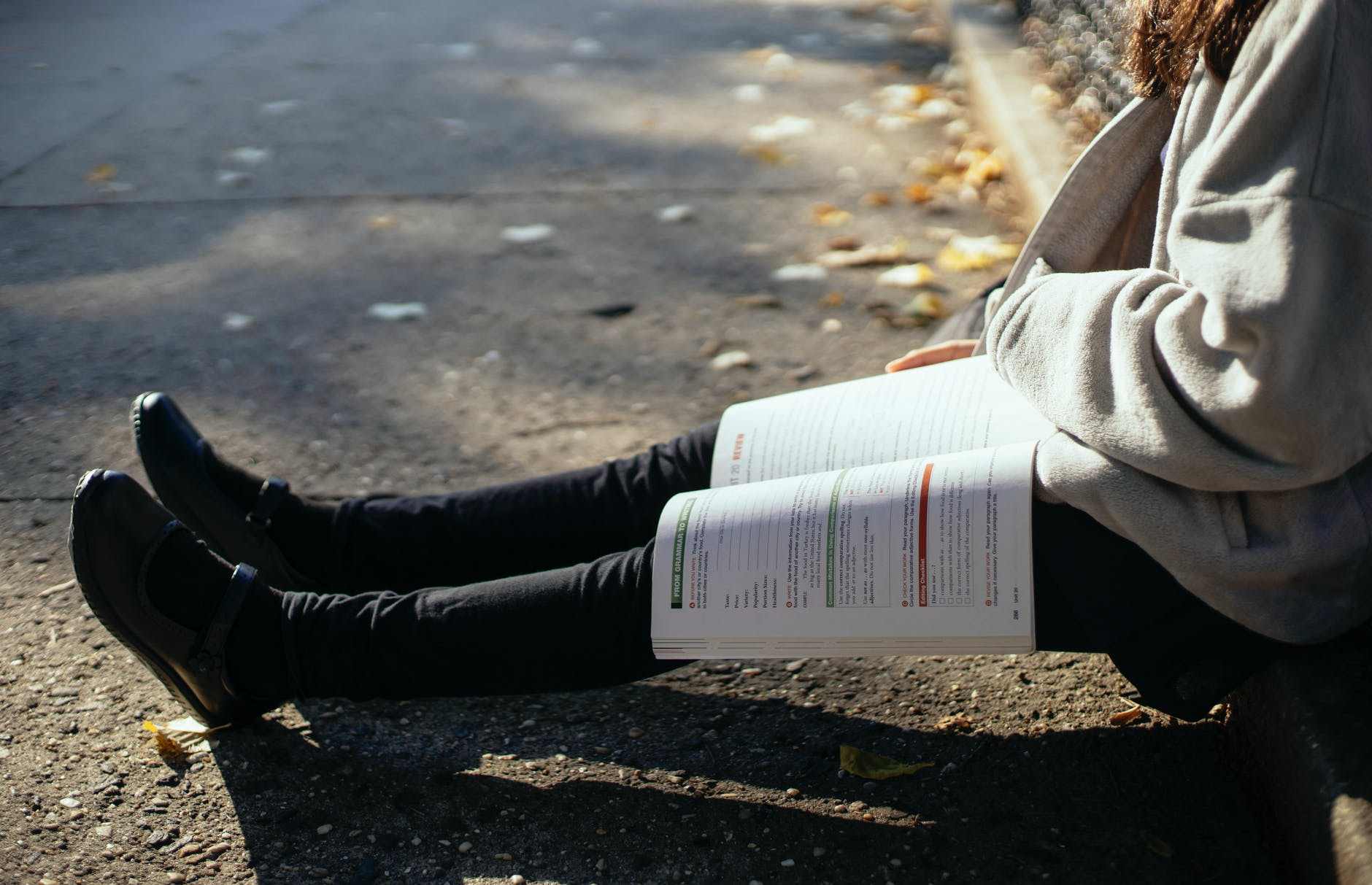 A woman is sat on the pavement curb with a textbook open on her lap.