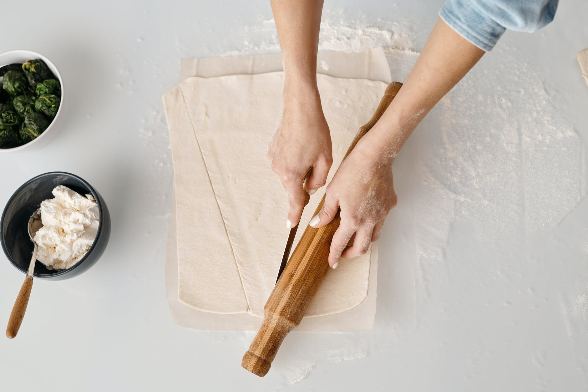 A woman cuts pastry and rolls it with a rolling pin.