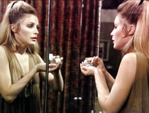 One of the women from 'Valley of the Dolls' stares at herself in the mirror and pours pills into her hand.
