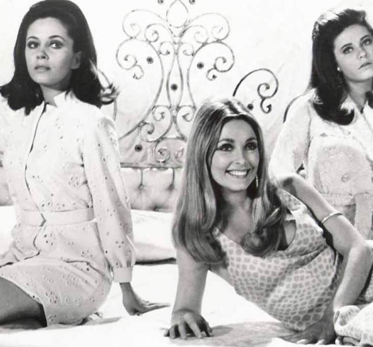 Three women sit on a bed together, only one of them smile at the camera