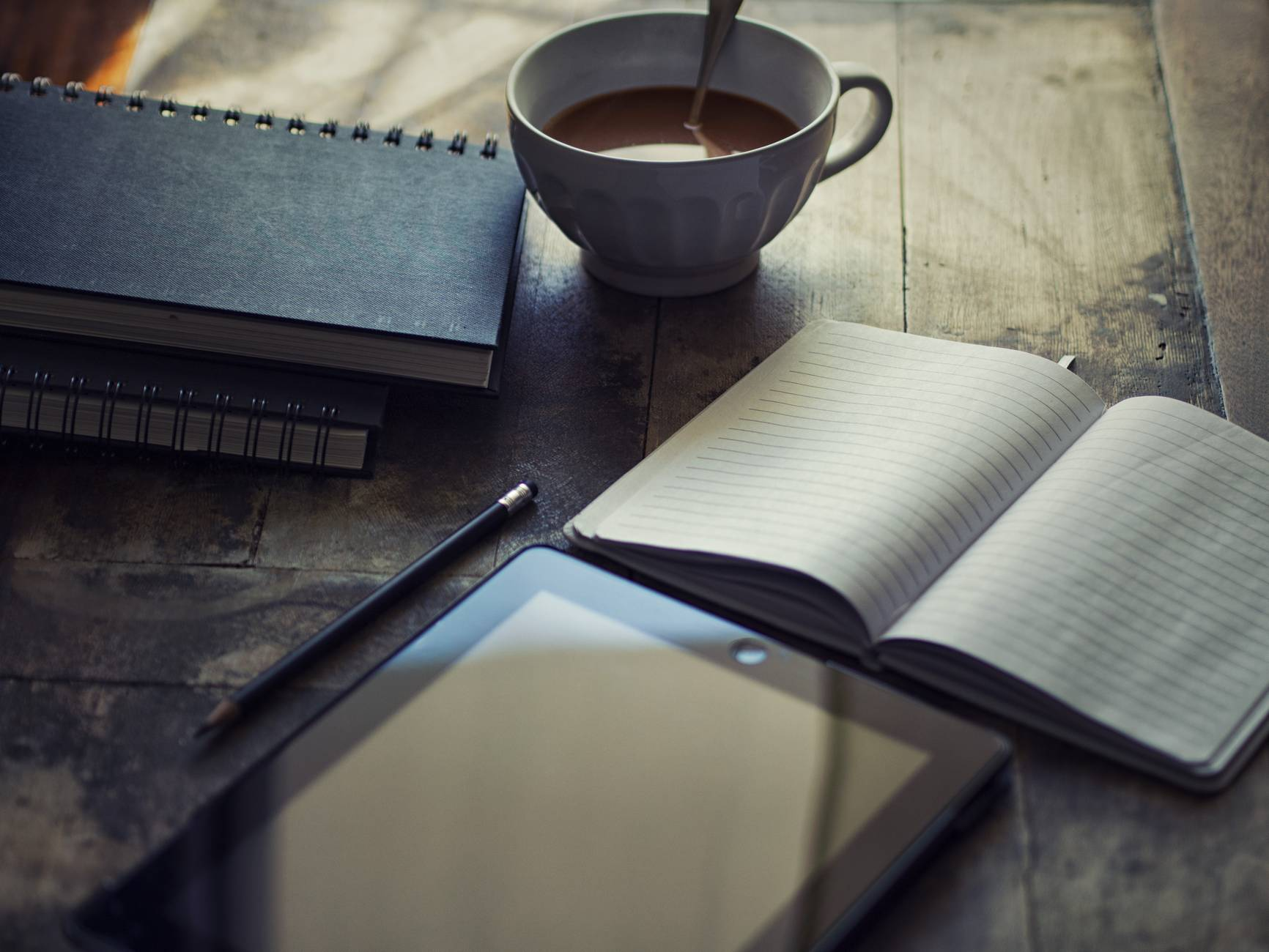 Black tablet and notebook on a table, with a drink of coffee.