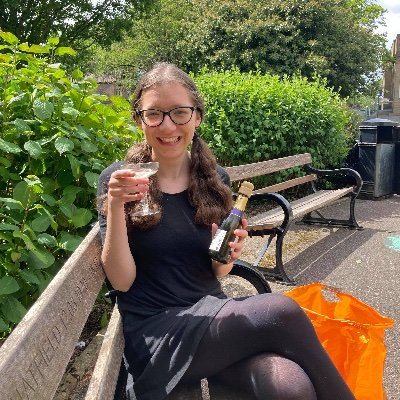 Me celebrating in the park after my exams. I hold a glass of prosecco and sit on a bench.