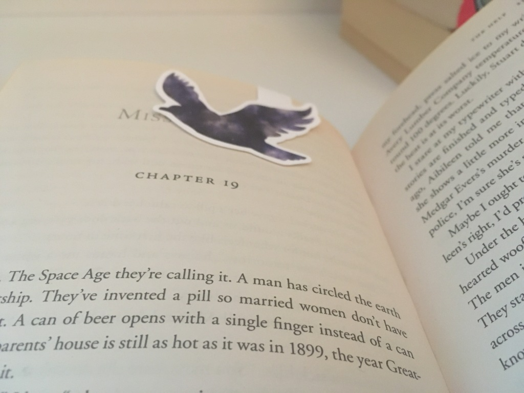 The open page of a book with a purple magnetic bird bookmark on the top of the page.