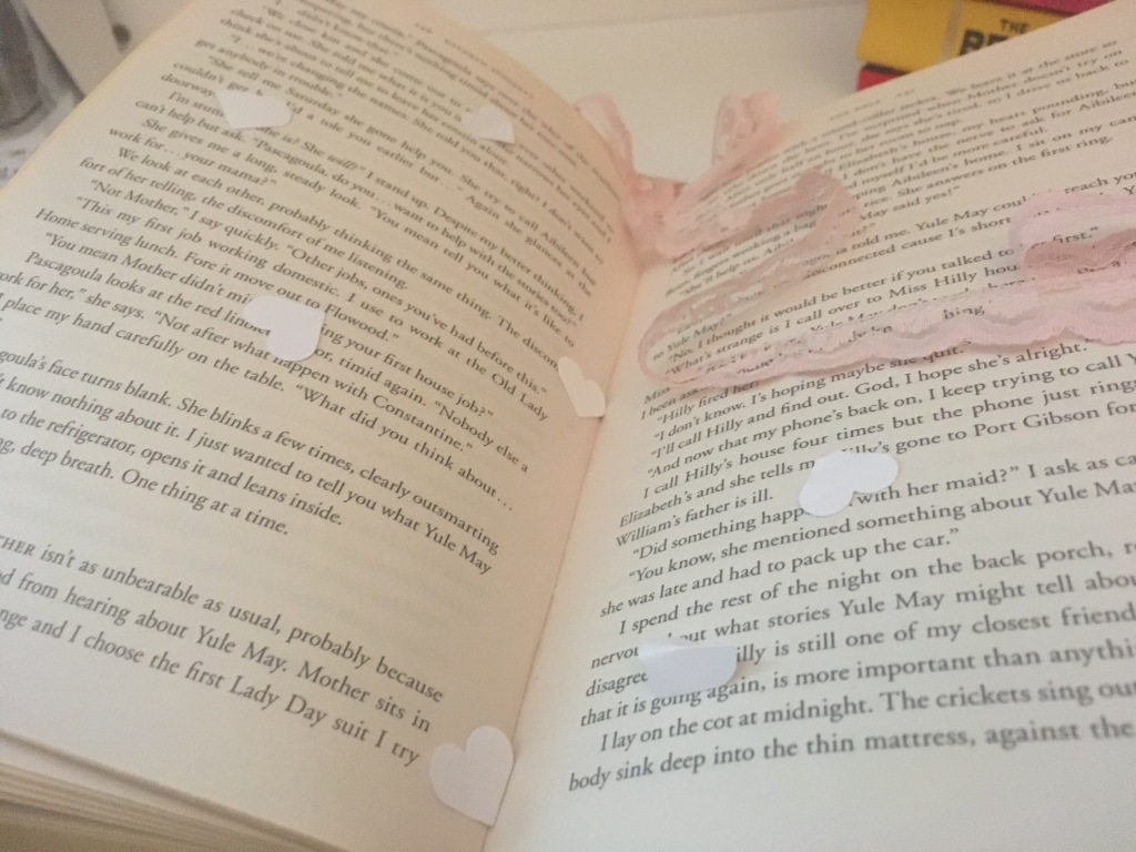 Open book with paper hearts sprinkled on the pages. A pink ribbon is laying on the pages.