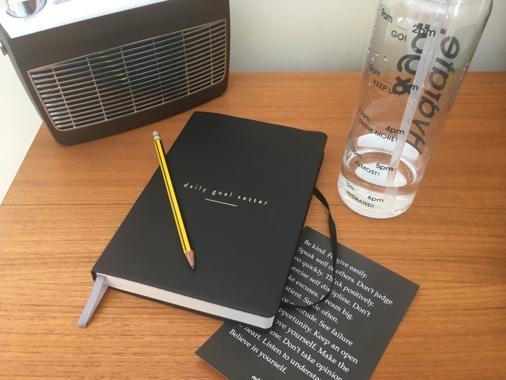 Mal Paper Planner with a radio and water bottle in the background.