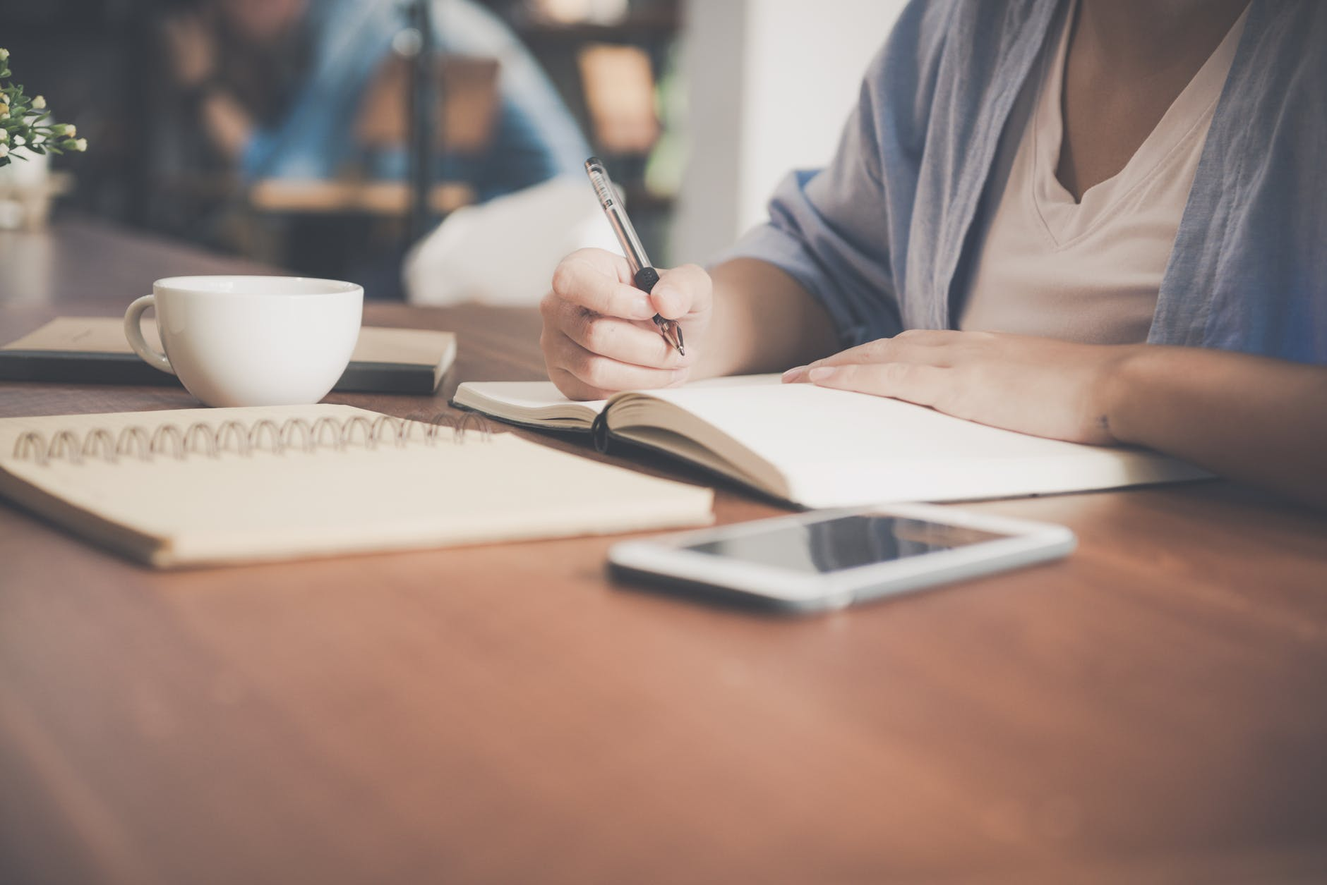 A woman writes in a notebook, with a coffee next to her.