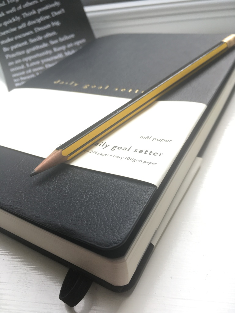 The cover of the Mal Paper Journal and a pencil.
