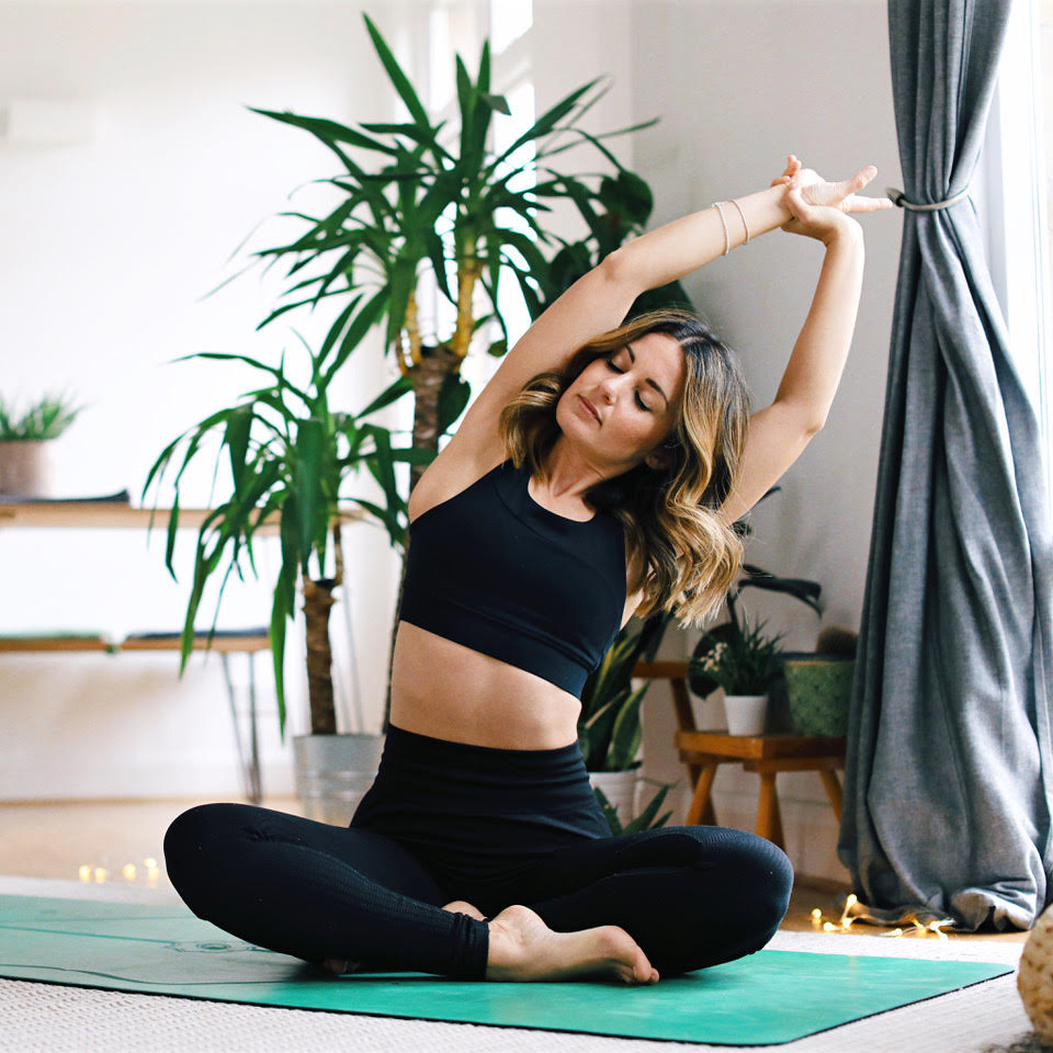 A woman sits on a yoga mat and stretches out her arms.