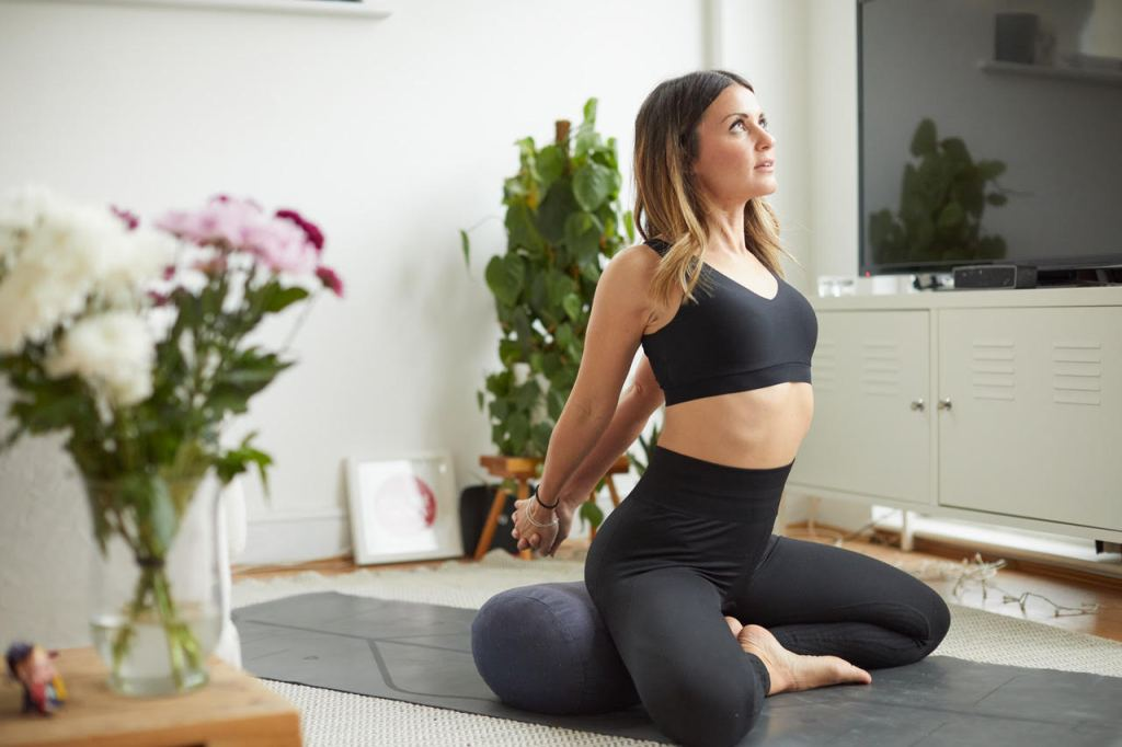 A woman kneels on her yoga mat and stretches her arms back.