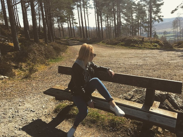 Woman poses on a bench and stares into a forest