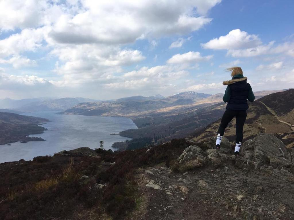 Woman stands on the edge of a hill