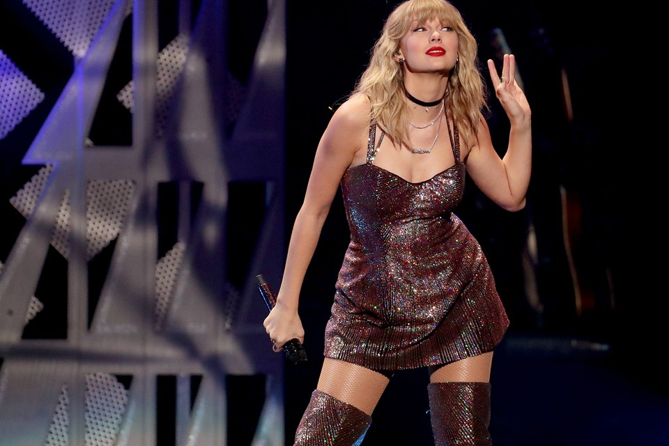 Taylor Swift performs on the stage for her fans, wearing a brown glittery dress and boots.