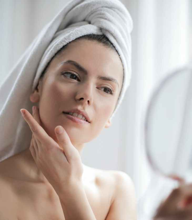 Woman inspects her face in the mirror