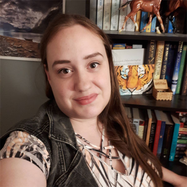 Woman takes a selfie in front of her book shelf
