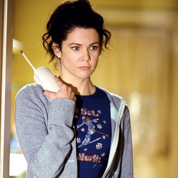 Lorelai Gilmore from 'Gilmore Girls' holds the phone to her shoulder and stares into space.