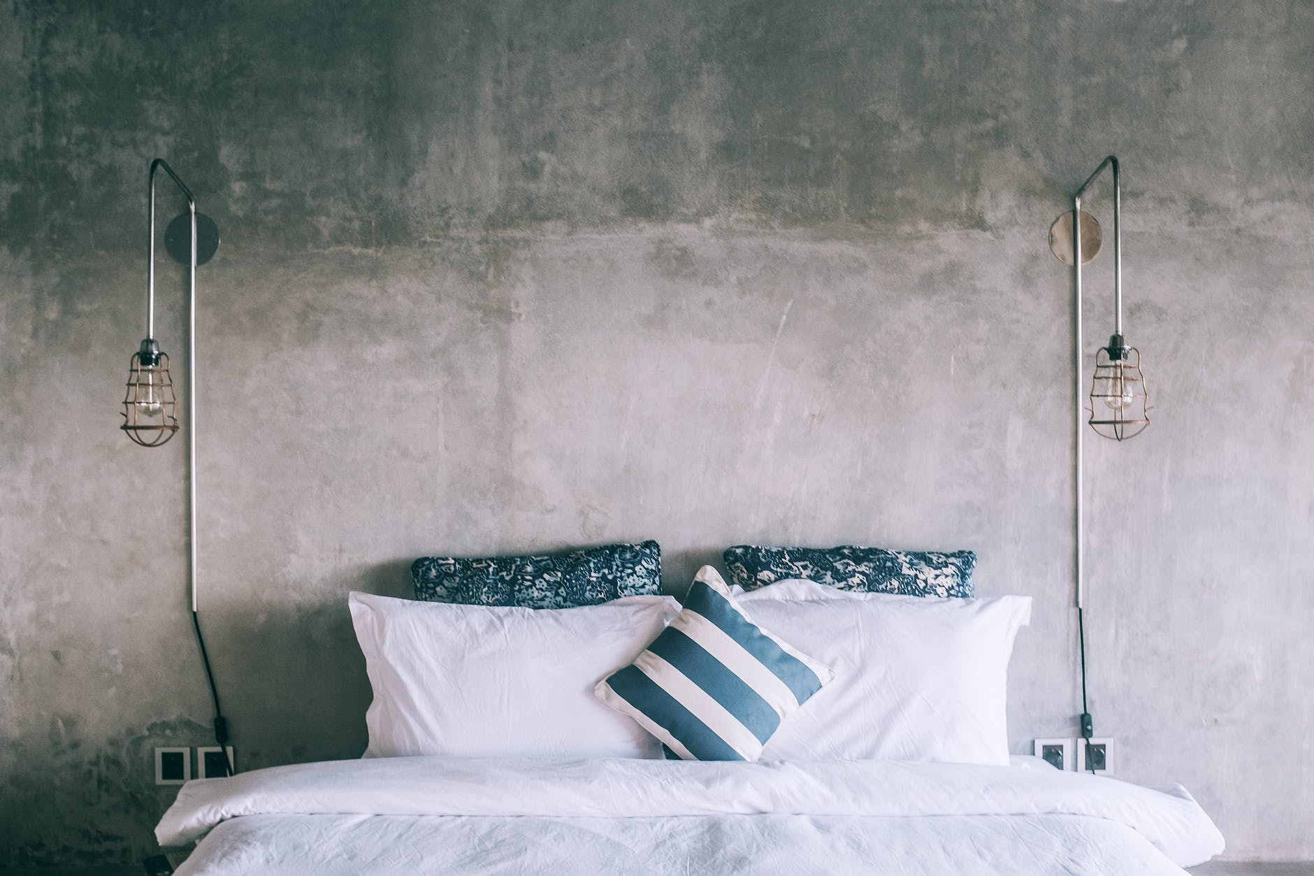 Double bed with a blue cover and pillows.