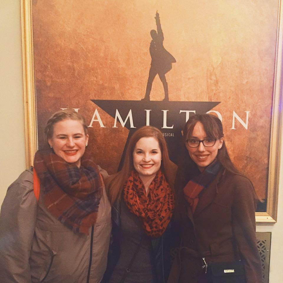 Three friends stand together in front of a poster for 'Hamilton'.