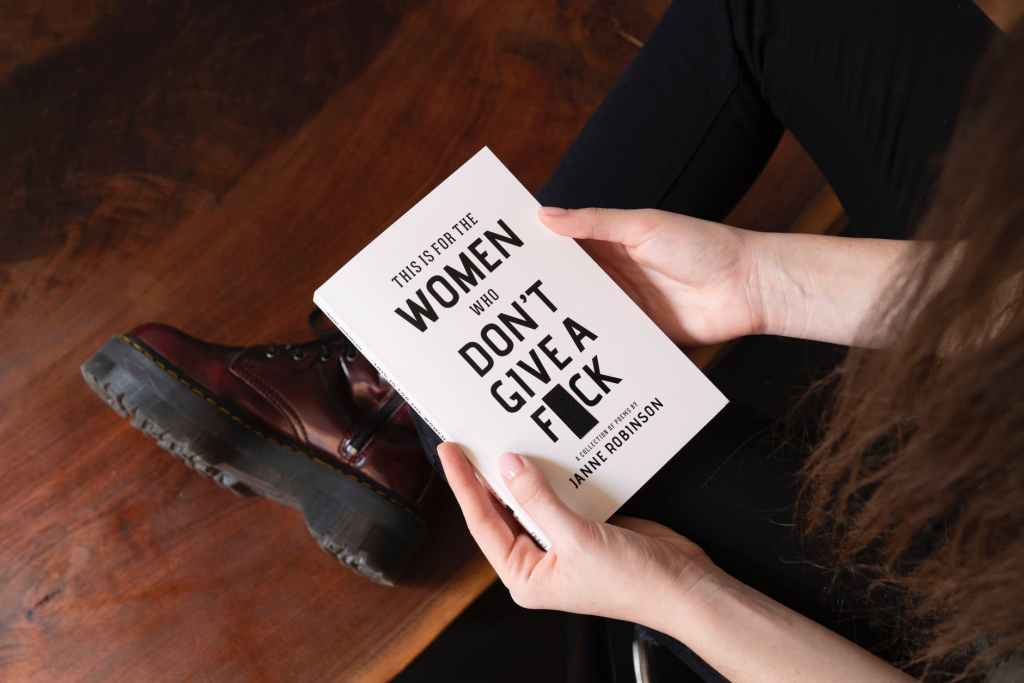 "A woman holds a book entitled ""This is for the Women who don't give a f**k""."