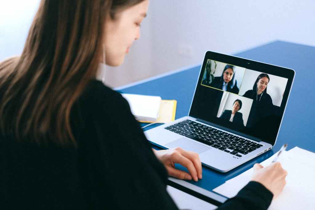 A woman has a video call with colleagues.