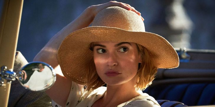 The New Mrs De Winter holds her straw hat and looks out of the car.