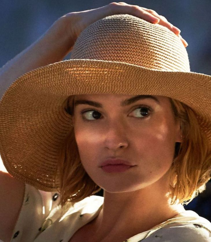 The new Mrs Dewinter sits in a car, holding her hand to her straw hat. She is played by Lily James