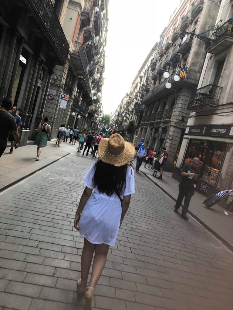 A young woman walks down a cute street with her back to the camera, wearing a straw hat.