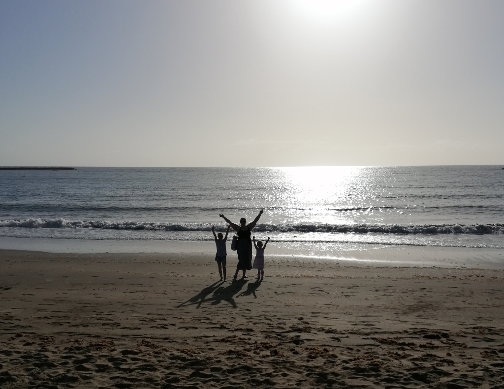 A man and his two children stand with raised arms by the sea, they are just silhouettes.
