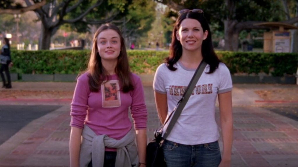 Lorelai and Rory Gilmore from the series 'Gilmore Girls' stare into the distance, smiling.