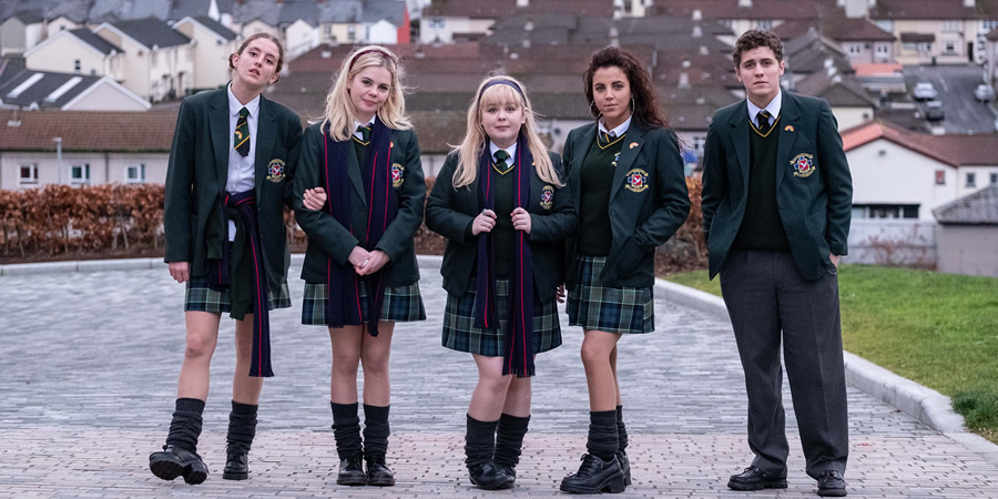 The characters from the series 'Derry Girls' stand in uniform and pose for the camera.