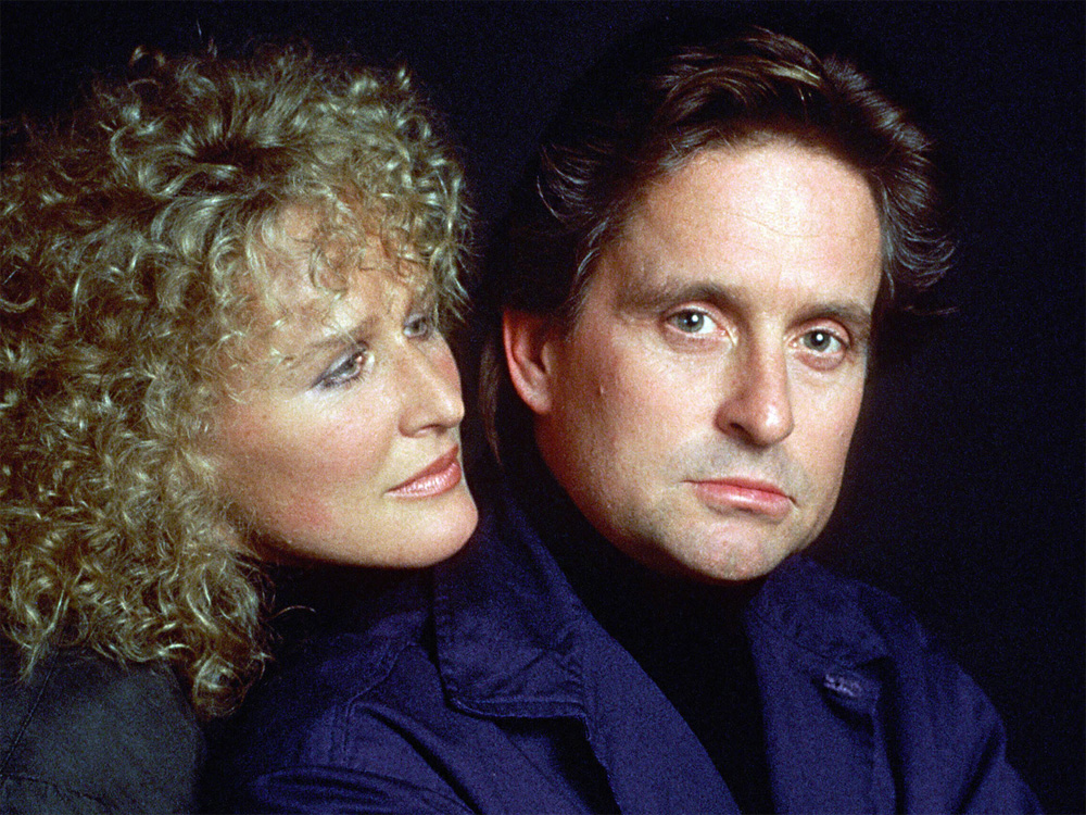 The two characters from 'Fatal Attraction' embrace. The man looks at the camera with concern.