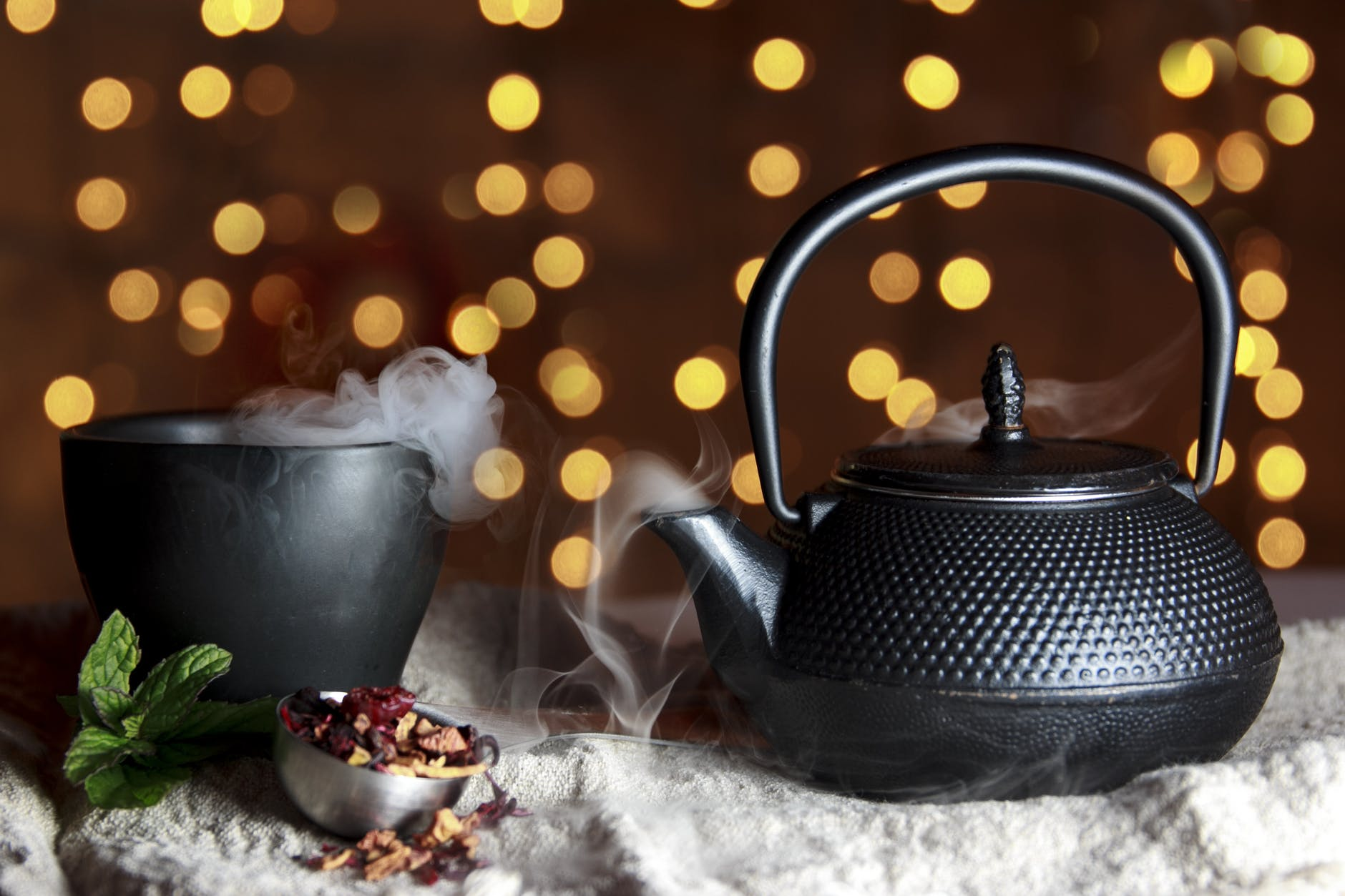 Kettle smokes next to a hot drink.