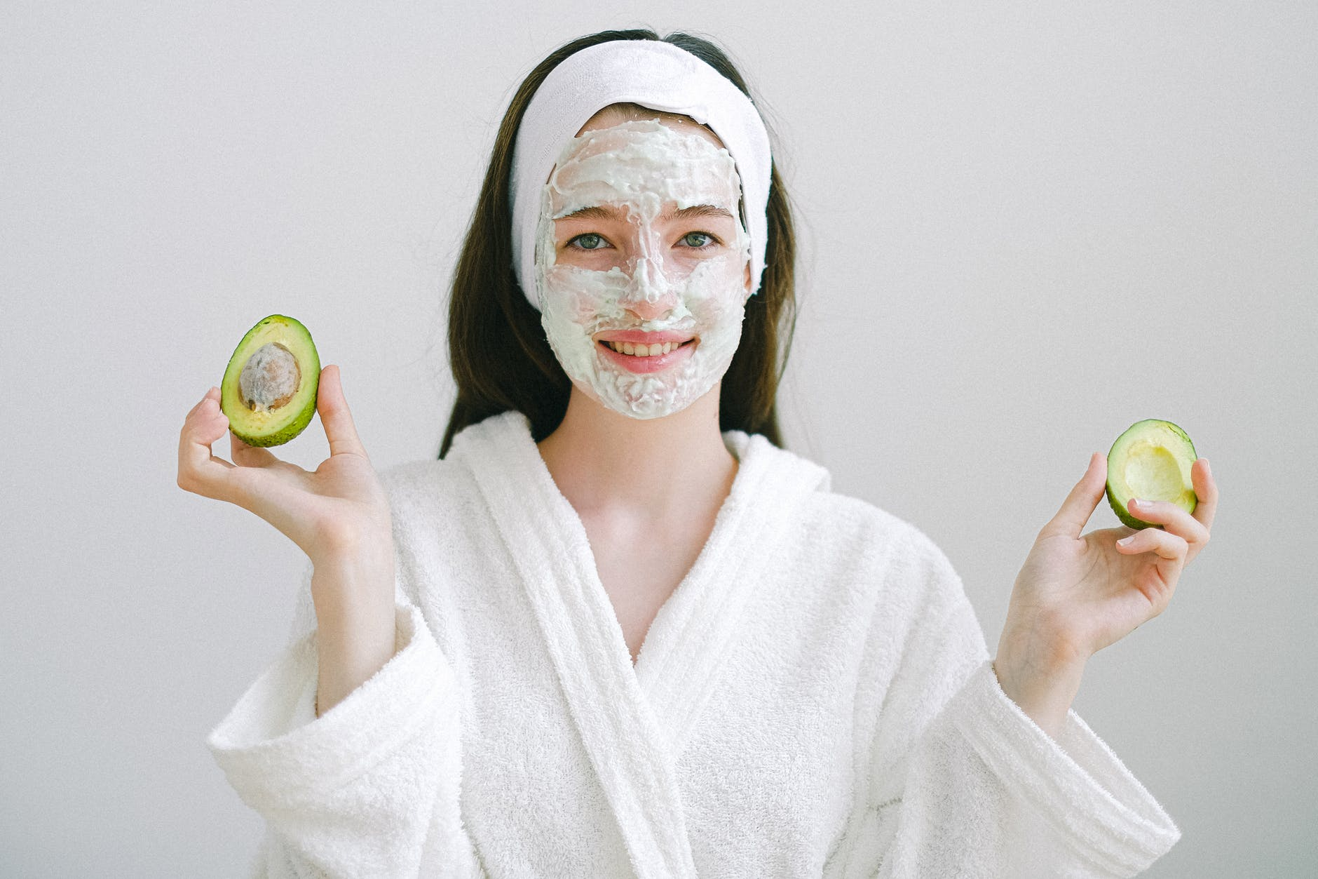 Woman wears a self-care homemade face mask and holds an avocado.