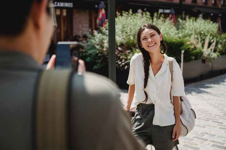 A man takes a photo of a woman while she poses and smiles.