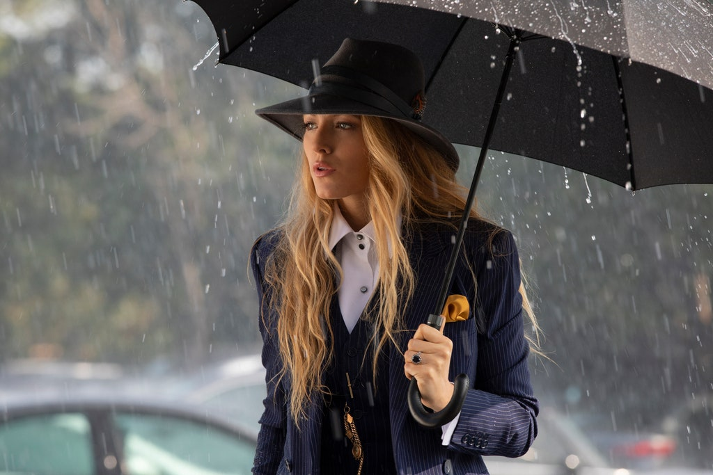 The main character, Emily, holds an umbrella to protect herself from the rain. She looks mysteriously into the distance.