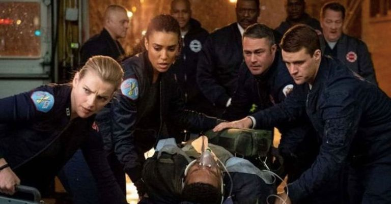A still from the series 'Chicago Fire' where the characters help an unconscious man.