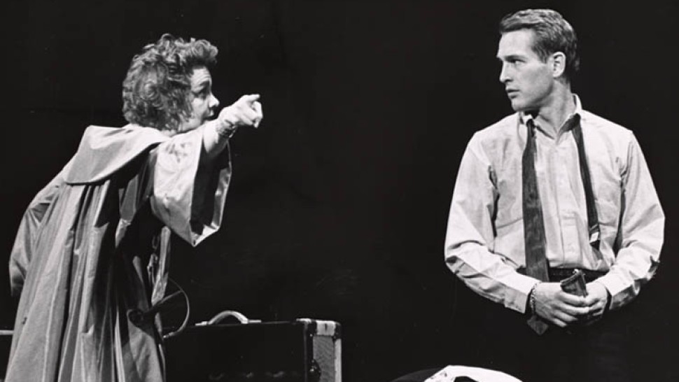 The two main characters argue, both look sad and the woman points into the distance, as if suggesting the man should leave.