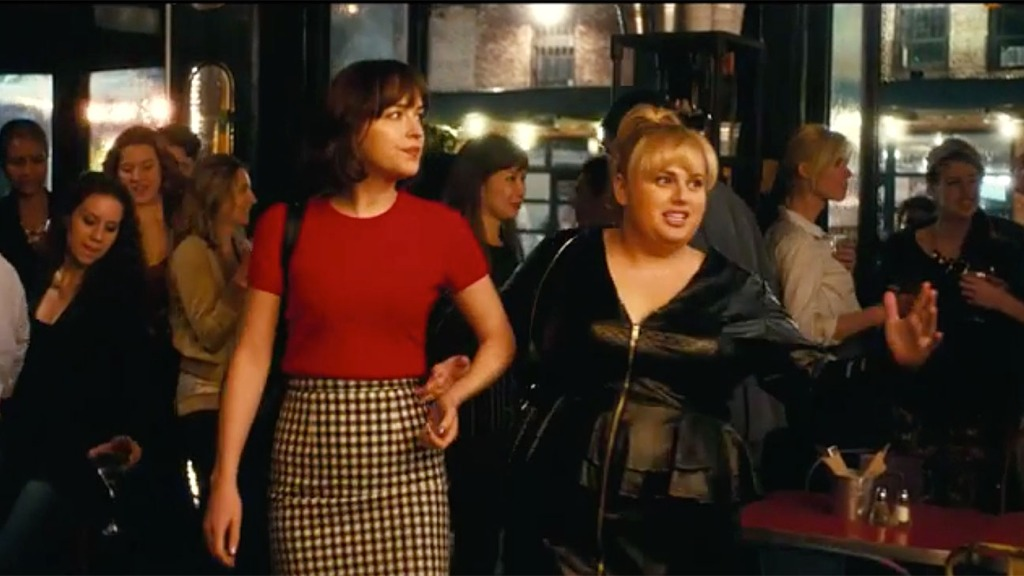The two main characters of the film 'How to be Single' walk into a busy bar.