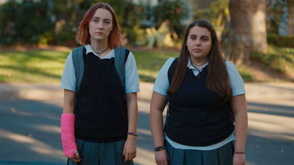 Ladybird and her best friend look at the screen blankly. Ladybird has a cast on her arm, and both wear school uniforms.