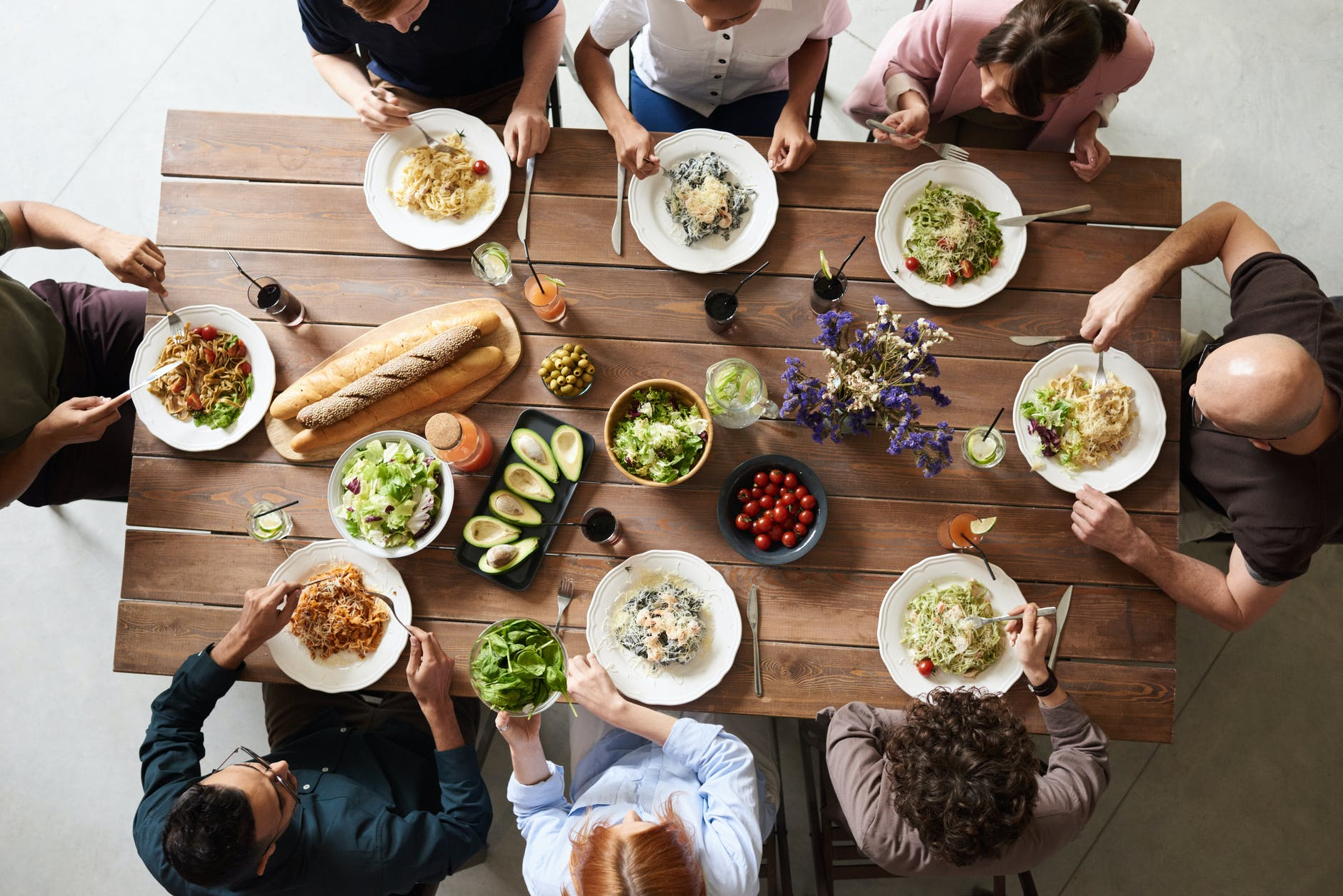 A dinner party, 8 people sit around a table and eat lunch from plates.