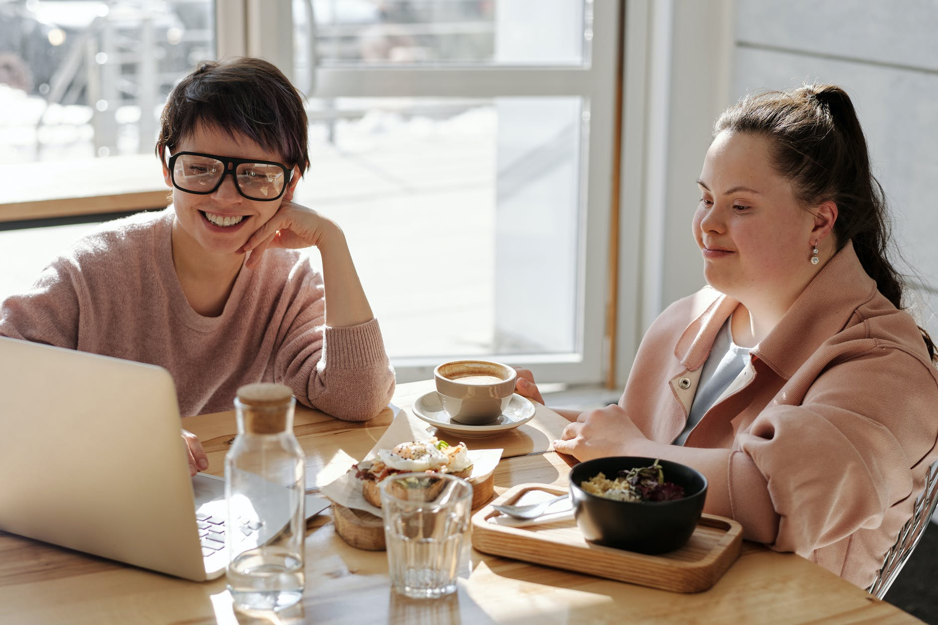 Two women chat and use a laptop.